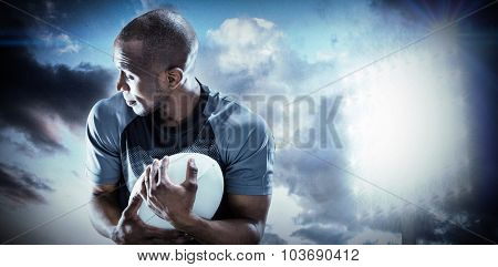 Rugby player looking away while catching ball against spotlight in sky