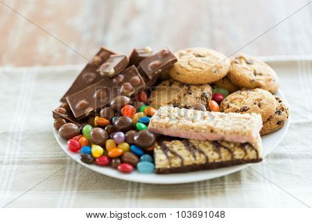junk food, sweets and unhealthy eating concept - close up of chocolate, oatmeal cookies, candies and muesli bars on plate