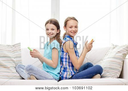 people, children, technology, friends and friendship concept - happy little girls with smartphones sitting on sofa back to back at home