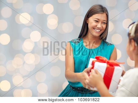 holidays, birthday family, childhood and people concept - happy mother giving present to her daughter rover holidays lights background