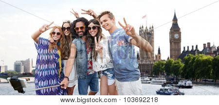summer vacation, travel, tourism, technology and people concept - smiling young hippie friends taking picture by smartphone selfie stick over london city and big ben tower background