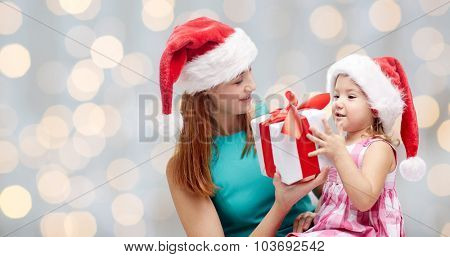 christmas, family, childhood and people concept - happy mother and little girl in santa hats with gift box over holidays lights background