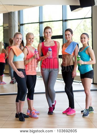 fitness, sport, training, gym and lifestyle concept - group of women with bottles of water in gym