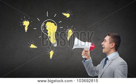 business, people, idea and announcement concept - happy businessman in suit speaking to megaphone and light bulbs over dark gray concrete wall background