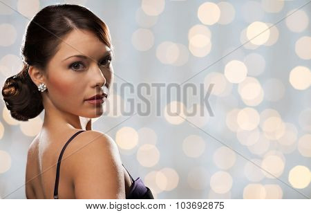 people, holidays, jewelry and luxury concept - woman face with diamond earring over lights background