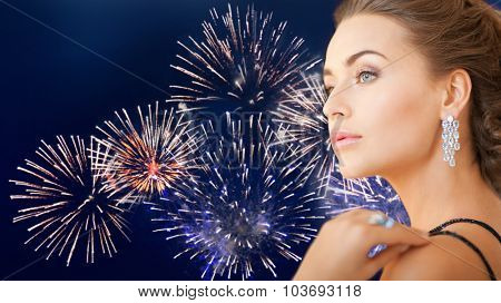 people, holidays and glamour concept - beautiful woman with diamond earring over firework on dark blue background