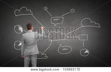 business, people and cloud computing concept - businessman drawing cloud computing scheme over dark gray concrete wall background