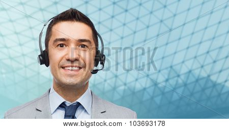 business, people, technology and service concept - smiling businessman in headset over city background