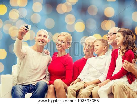 family, holidays, generation, christmas and people concept - smiling family with camera taking selfie and sitting on couch over blue lights background