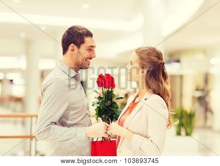 relations, love, romance and people concept - happy young couple with flowers talking in mall