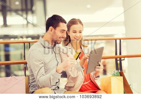 sale, consumerism, technology and people concept - happy young couple with shopping bags and credit card pointing finger to tablet pc computer in mall