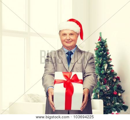 business, presents and people concept - smiling senior man in suit and santa helper hat with gift over living room and christmas tree background