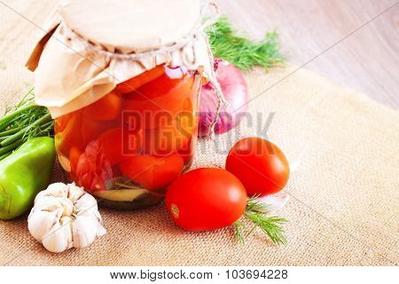 Tomatoes Marinated In Jars With Spices And Vegetables On A Table