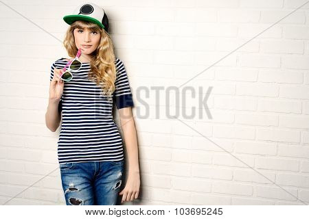 Joyful teen girl in casual clothes and sunglasses posing by a brick wall. Active lifestyle. Youth fashion. Studio shot.