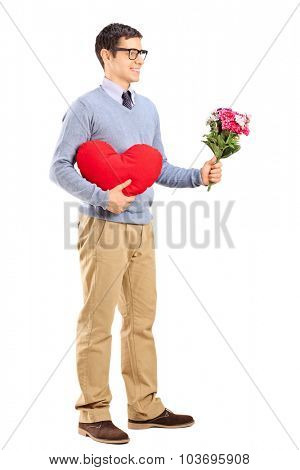 Full length portrait of a romantic man holding a red heart and a bouquet of flowers isolated on white background