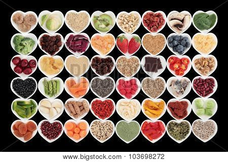 Large superfood fruit and vegetable selection in heart shaped dishes over black background. High in antioxidants, vitamins, protein and dietary fibre.