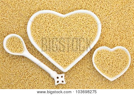 Pearl couscous food in heart shaped bowls and porcelain spoon forming an abstract background.