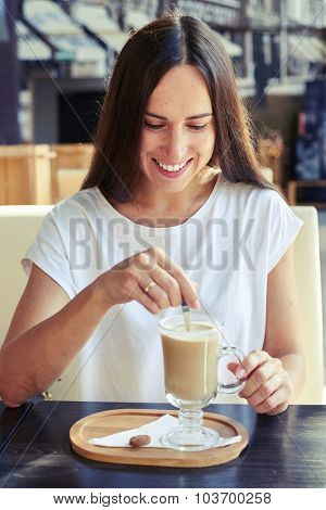 attractive smiley woman sitting in cafe and looking at her cappuccino
