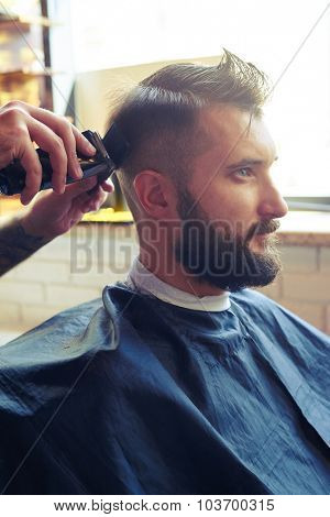 sideview portrait of handsome man in a barber shop. barber cutting hair with electric clipper and comb