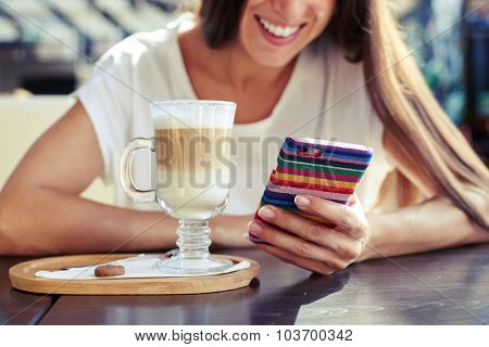 laughing young woman using her smartphone and sitting in cafe