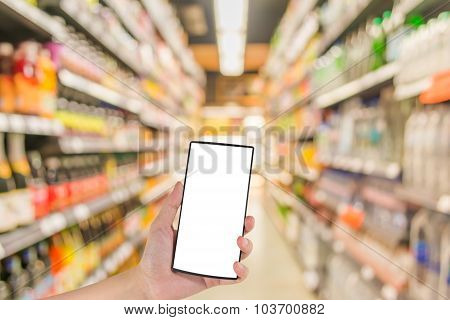Male Hand Is Holding A Modern Touch Screen Phone And  Blurred Image Of Supermarket .