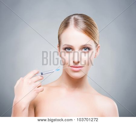 Attractive young woman injecting treatment into skin.