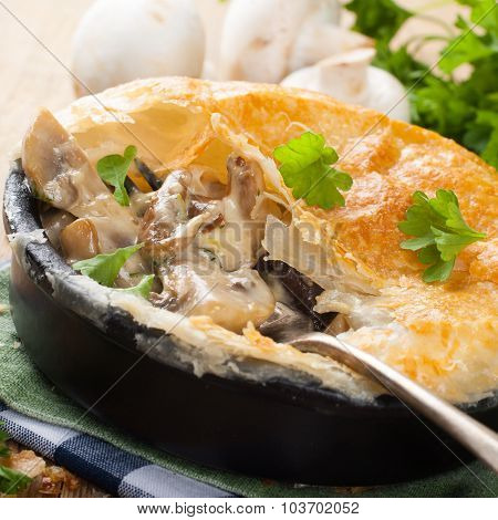 Stewed mushrooms under puff pastry.