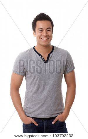 Portrait of happy smiling casual Asian man standing hands in pockets.
