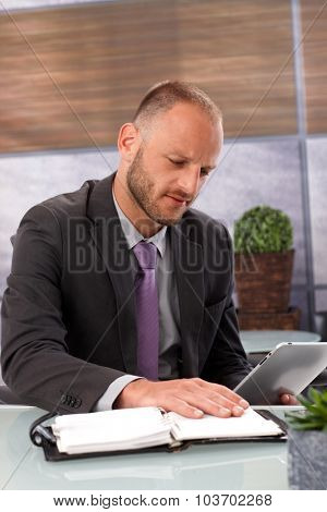 Businessman sitting at desk in office, hesitating between tablet computer and personal organizer.