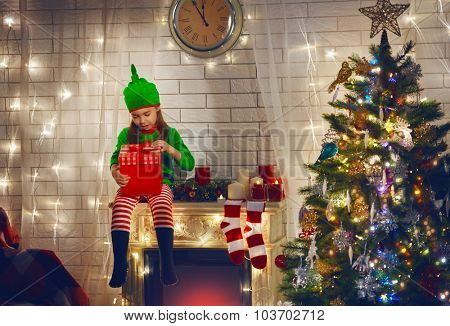 Little girl in costume of Christmas elf sitting on the fireplace and holding a gift in hands