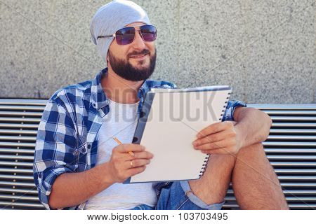 smiley bearded man in sunglasses sitting on bench and holding white notepad