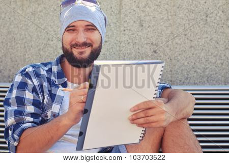 portrait of stylish young adult man with white notepad