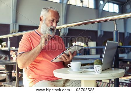 thoughtful senior man looking at notepad in cafe