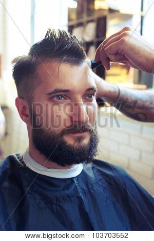 portrait of handsome man with beard in barber shop. barber cutting hair with scissors and comb
