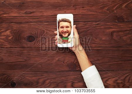 womans hand holding smartphone with incoming call on the screen over wooden brown  background
