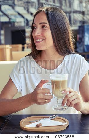 attractive smiley woman holding cup of cappuccino in cafe