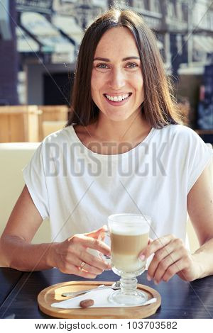 cheerful woman in white t-shirt sitting in cafe, holding cup of cappuccino and looking at camera