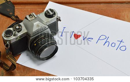 Model of Pentax K 1000 film camera on paper write I love pho