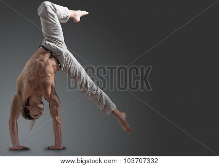 Sporty young man doing gymnastic exercise