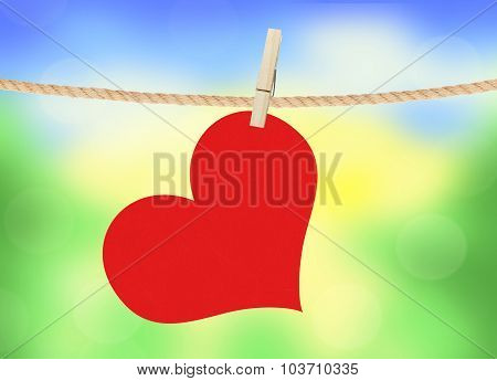 Red Heart Hang On Clothespin Over Bright Nature Background