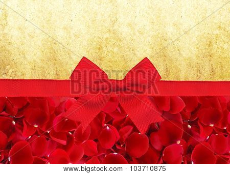 Red Rose Petals And Red Ribbon With Bow Over Old Paper Background