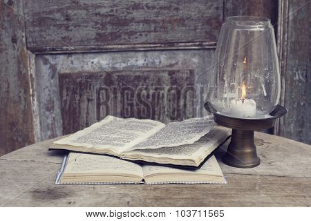 Open Book And Candlestick On A Vintage Wooden Table