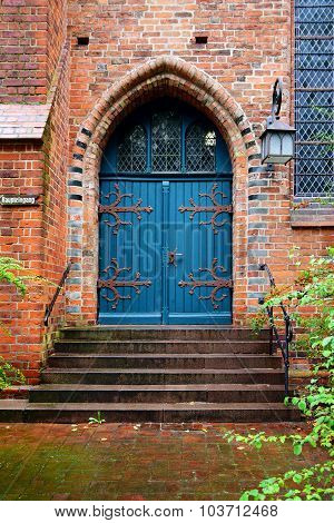 Blue Wooden Door, Entrance To An Old Brick Church