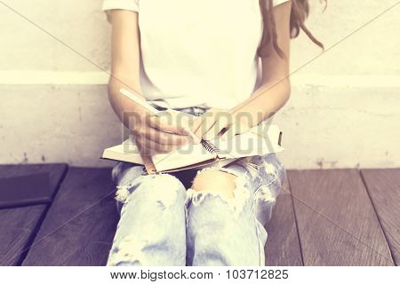 Schoolgirl Sitting On Floor And Wrote In A Diary