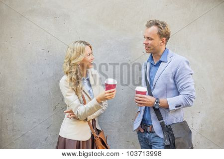 Man and woman standing by the wall and talking
