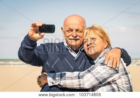 Senior Happy Couple Taking A Selfie At The Beach At End of Season - Elderly Concept