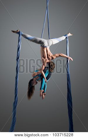 Sporty couple doing exercise with elastics aerial silk