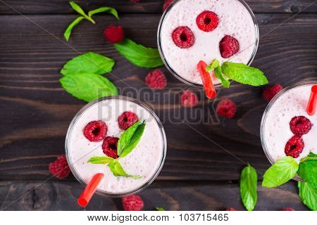 Milk cocktail with raspberry and mint in glass on a rustic wooden background