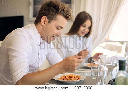 Young guys eating pasta