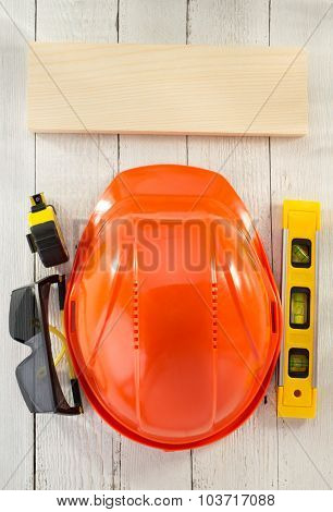 construction helmet and safety glasses on wooden background